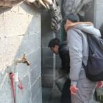 同学们正在用水桶接水冲洗狗舍