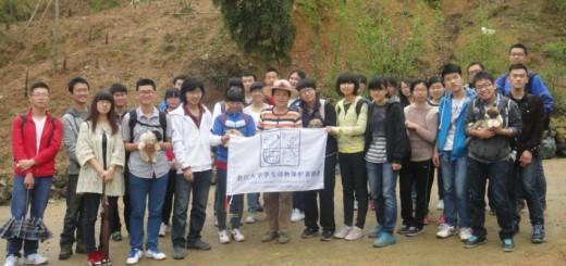 图片正中为王阿姨,旗帜左侧白色上衣者为会长